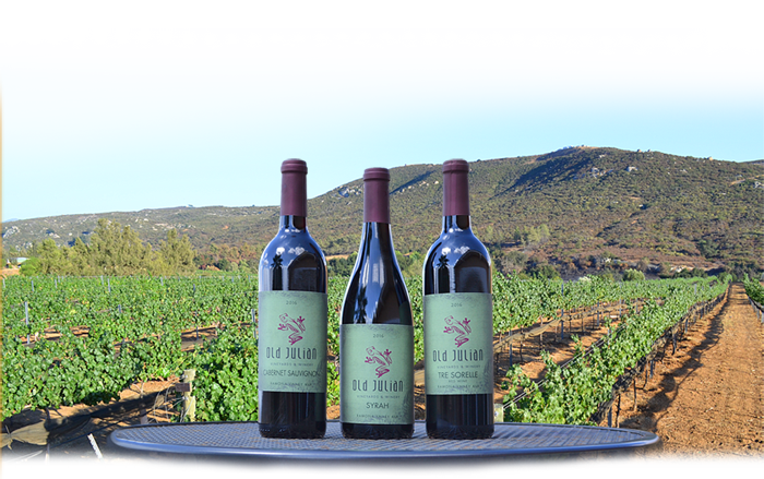 Wine bottles in front of a vinyard and rolling hills